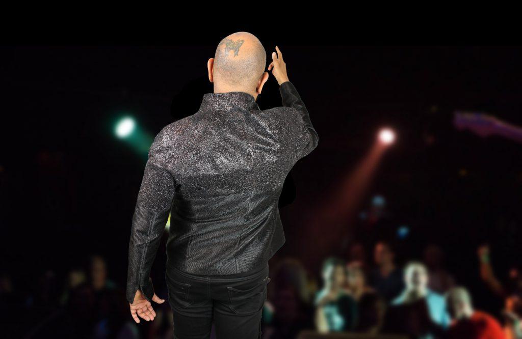 David Moore steht auf einer Bühne mit einer unglaublich intensiv funkelnden Jacke mit Glitter.